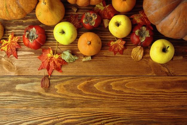 Un mazzo di zucche e mele. raccolga o fondo di ringraziamento con i frutti e le zucche autunnali sulla tavola di legno rustica.