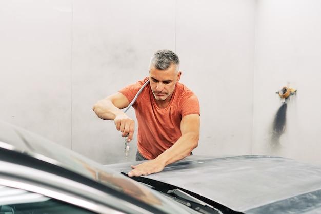 Un meccanico che prepara un'auto per dipingerla