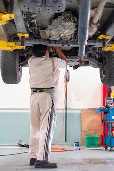 Un meccanico in piedi sotto la macchina che si trova sulla piattaforma di sollevamento, riparazione auto