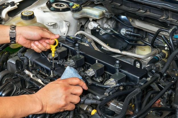 Un meccanico professionista tiene in mano l'astina di livello dell'olio e controlla il livello dell'olio nel motore dell'auto