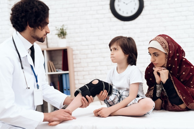 Un medico arabo ha vestito una benda sulla gamba di un bambino.