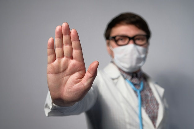 Un medico asiatico o cinese in una maschera medica e occhiali mostra un segnale di stop con la mano.