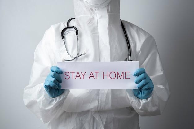 Un medico con una carta con stare a casa tenendo a portata di mano, protegge dal coronavirus o dall'epidemia di covid-19
