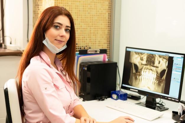 Un medico dentista femmina è seduto a un tavolo, su un computer