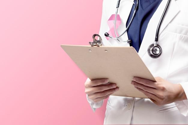 Un medico donna in un camice bianco da laboratorio con un nastro rosa e uno stetoscopio tenendo appunti con uno sfondo rosa
