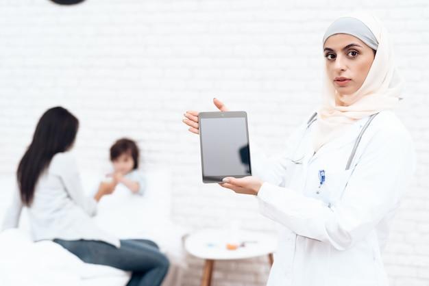 Un medico femmina in hijab posa sulla fotocamera.