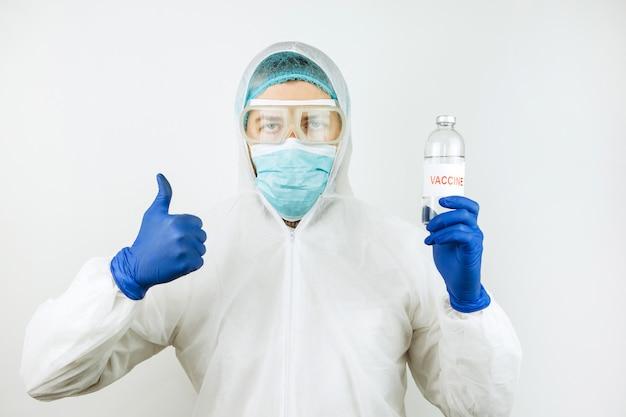 Un medico in camice bianco e guanti blu tiene una provetta per siringa con un vaccino contro il coronavirus. iniezione di vaccino covid 2019. 2020 coronavirus pandemico. test del vaccino.