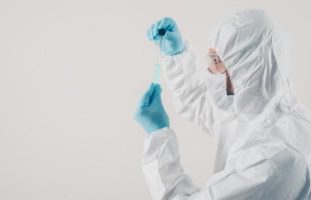 Un medico in piedi e in possesso di medicina in guanti medici e tuta protettiva in sfondo chiaro.