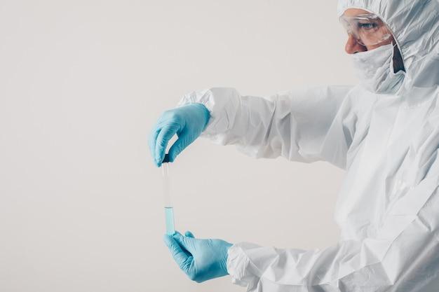 Un medico in piedi e in possesso di medicina in sfondo chiaro in guanti medici e tuta protettiva.