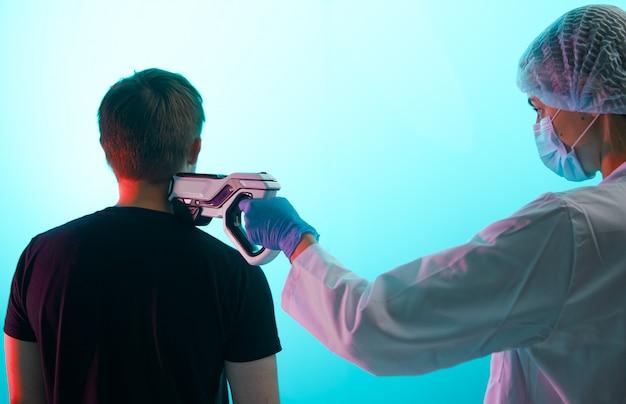 Un medico inocula un paziente maschio con una pistola per iniezione, nel collo, in primo piano