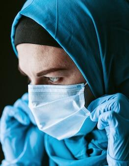 Un medico, una donna musulmana in un hijab e una benda medica protettiva