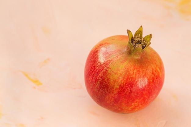 Un melograno rosso maturo su una rosa