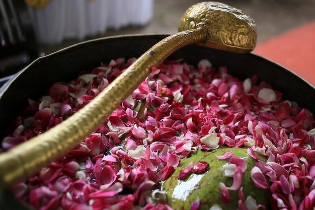 Un mestolo d'acqua dorata e una grande ciotola di rame piena d'acqua e piena di fiori su panggih