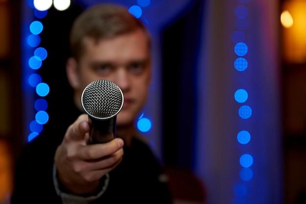 Un microfono nella mano tesa di un giovane uomo sfocato. copi lo spazio.