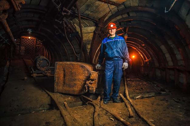 Un minatore in una miniera di carbone si trova vicino a un carrello. copia spazio