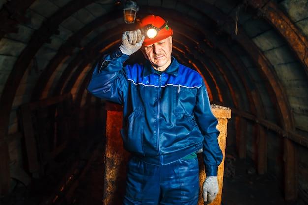 Un minatore in una miniera di carbone si trova vicino a un carrello. copia spazio.