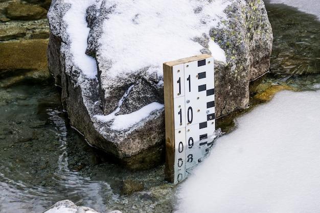 Un misuratore del livello dell'acqua viene utilizzato per monitorare il livello dell'acqua. in un lago ghiacciato