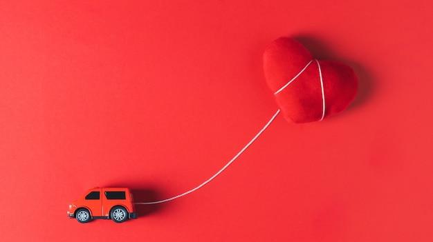 Un modello di auto rossa che rimorchia un cuscino cuore rosso su uno sfondo rosso, concetto, tema di san valentino