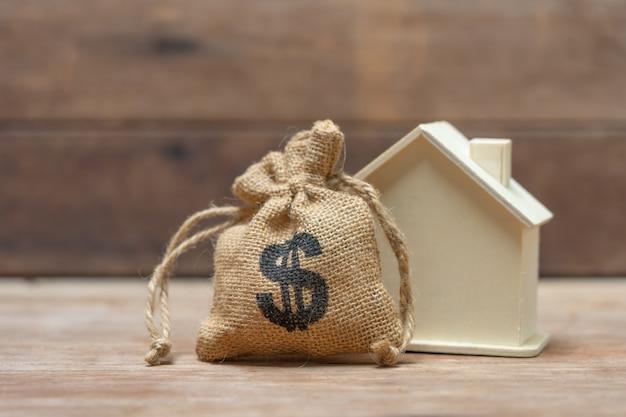 Un modello di casa modello è posto su una pila di monete