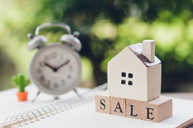 Un modello di casa modello è posto sulla vendita di parole in legno. come proprietà di sfondo