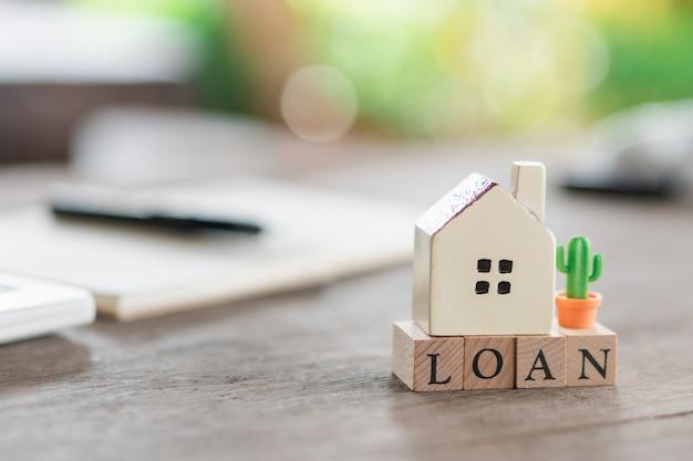 Un modello di casa modello viene posizionato su un messaggio di parola in legno del taccuino