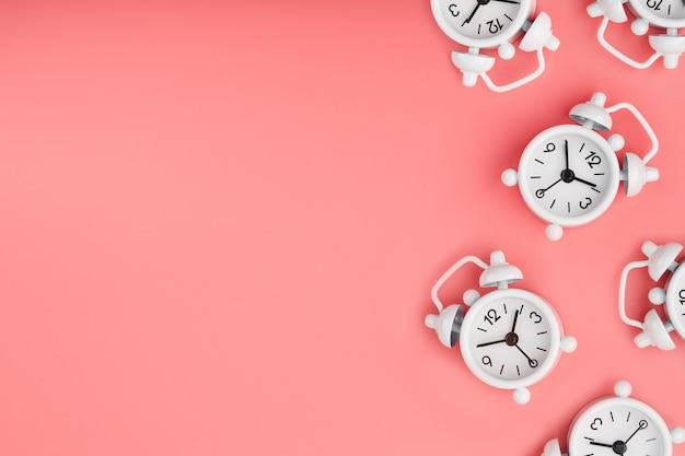 Un modello di molte sveglie classiche bianche sotto forma di un modello su uno sfondo rosa. vista dall'alto con una copia dello spazio, piatto disteso.