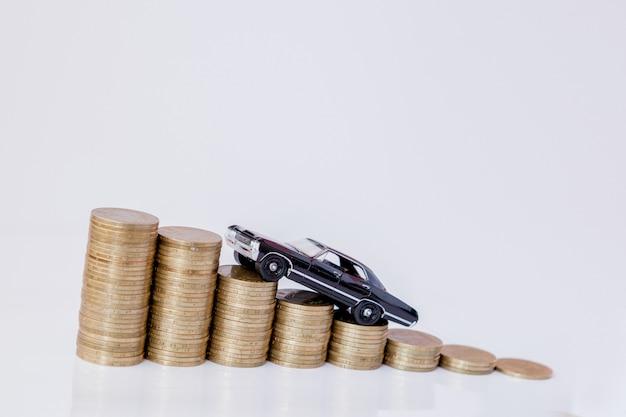 Un modello nero di un'auto con monete a forma di istogramma su uno sfondo bianco. concetto di prestito, risparmio, assicurazione.