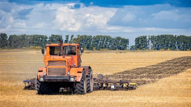 Un moderno trattore arancione ara il campo di grano dorato della terra