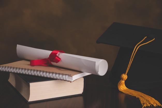 Un mortarboard di laurea sulla cima di una pila di libri, con rotolo di pergamena legato in nastro rosso.
