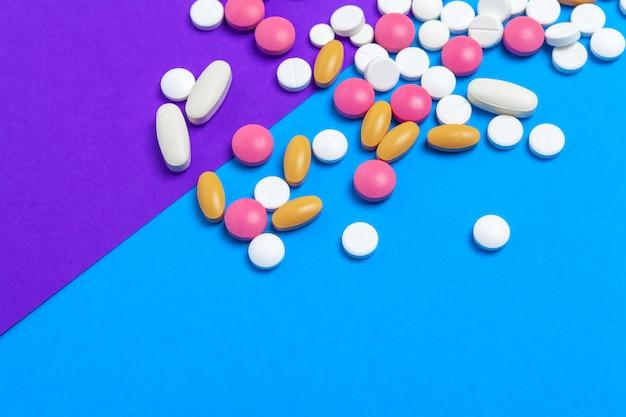 Un mucchio delle pillole multicolori sul blu. vista dall'alto.