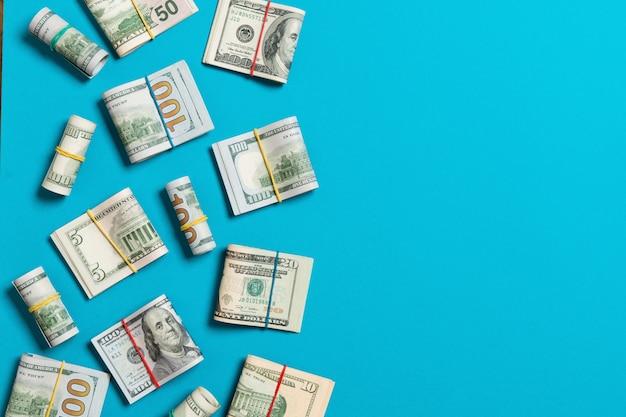 Un mucchio di cento soldi delle banconote in dollari americani su fondo blu