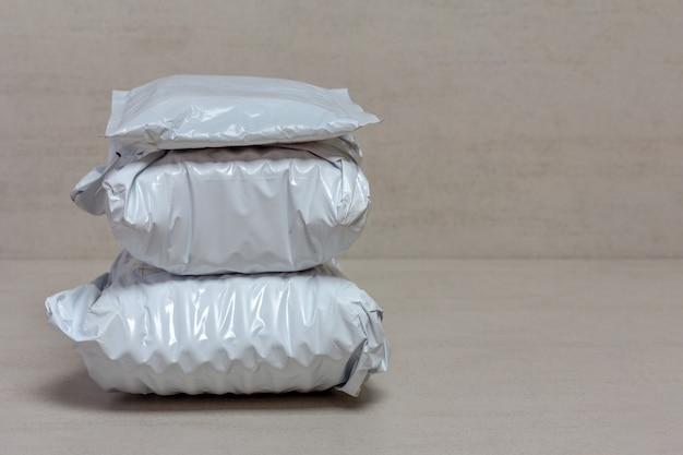 Un mucchio di pacchetti postali grigi da negozi cinesi si chiudono su uno sfondo grigio con spazio di copia