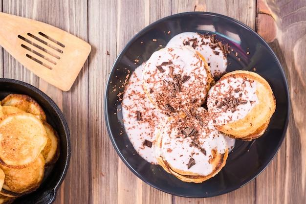 Un mucchio di pancake ripieni di yogurt alla frutta e cosparsi di cioccolato grattugiato su un piatto su un tavolo di legno