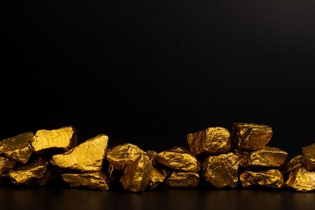 Un mucchio di pepite d'oro o di minerale d'oro su fondo nero