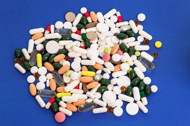 Un mucchio di pillole e capsule sparse su uno sfondo blu in diverse forme, dimensioni e colori. prevenzione e trattamento durante il periodo della pandemia di coronavirus. vista dall'alto.