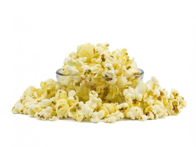 Un mucchio di popcorn in una ciotola di vetro isolata su un bianco