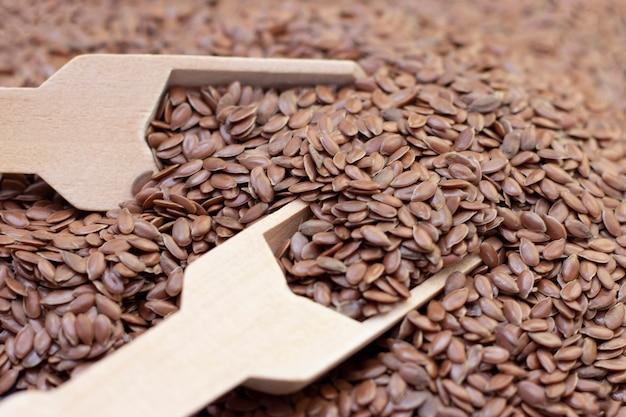 Un mucchio di semi di lino o di lino in un cucchiaio di legno su uno sfondo di pietra nera.