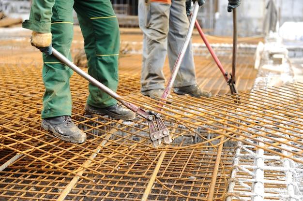 Un muratore che collega travi di ferro