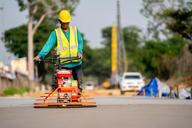 Un muratore che versa un concret bagnato al cantiere della strada