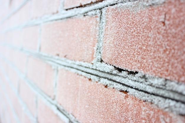 Un muro di mattoni congelati nella neve bianca