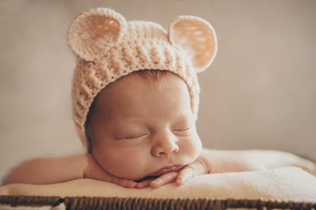 Un neonato con un cappello lavorato a maglia con orecchie. imitazione di un bambino nel grembo materno. ritratto di un neonato. il concetto di salute, genitorialità, festa dei bambini, medicina, fecondazione in vitro