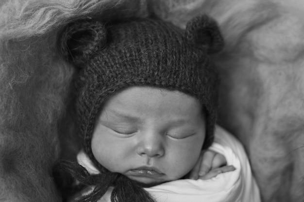 Un neonato in un cappello a maglia con orecchie. imitazione di un bambino nel grembo materno. ritratto di un neonato. il concetto di salute, genitorialità, festa dei bambini, medicina, fecondazione in vitro, moda