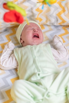 Un neonato piange nella culla a causa di coliche