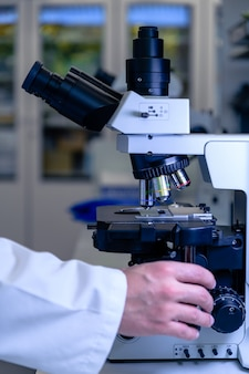 Un operaio di laboratorio che lavora con un microscopio moderno mentre conduce una ricerca