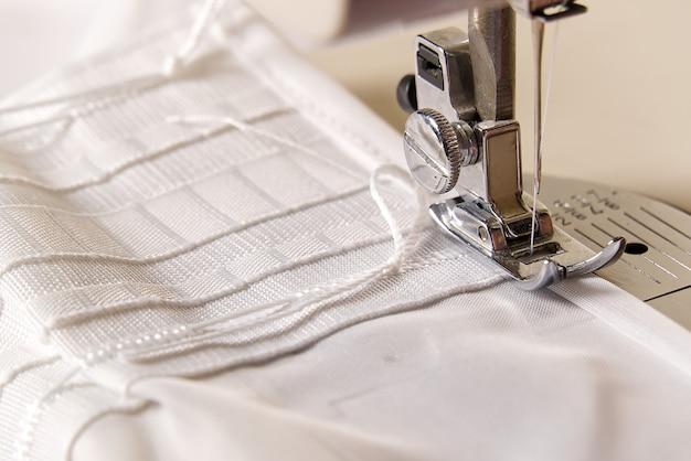 Un operaio lavora su una macchina da cucire. sarta cuce tende bianche, vista ravvicinata.