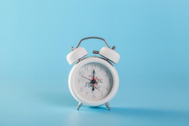 Un orologio bianco su una parete blu