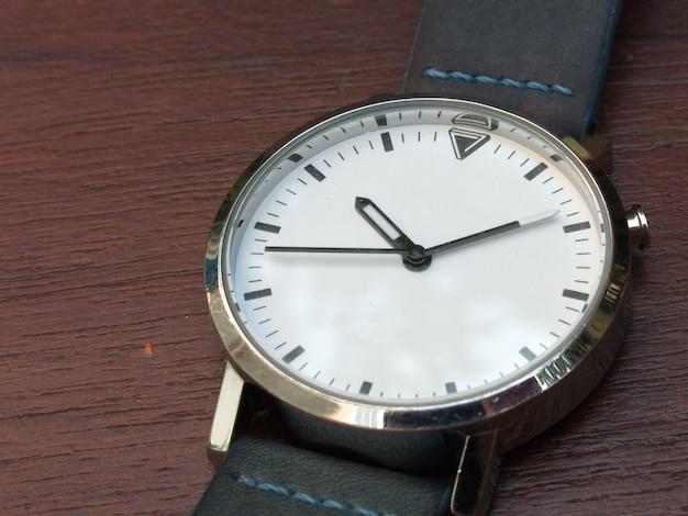 Un orologio bianco sullo sfondo marrone