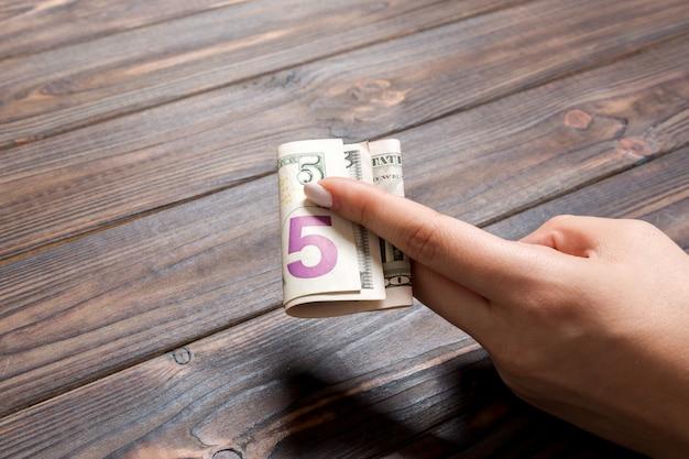 Un pacchetto di 5 banconote in dollari in mano femminile sul tavolo di legno. concetto di stipendio con spazio di copia