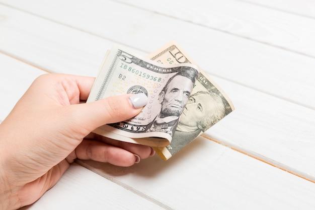 Un pacchetto di banconote da cinque e dieci dollari in mano femminile