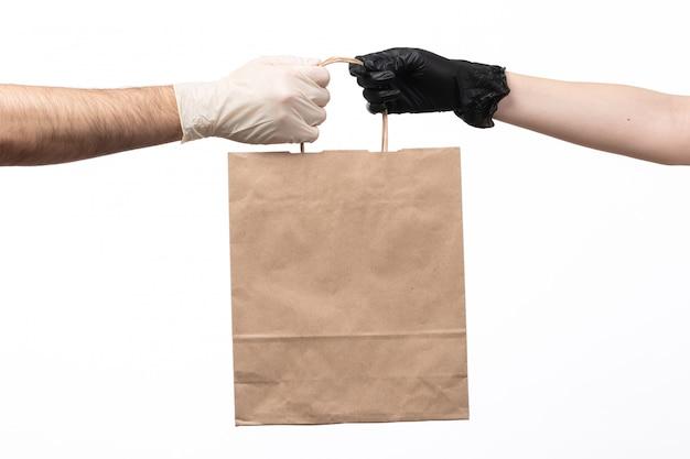 Un pacchetto di carta marrone vista frontale che viene consegnato da femmina a maschio